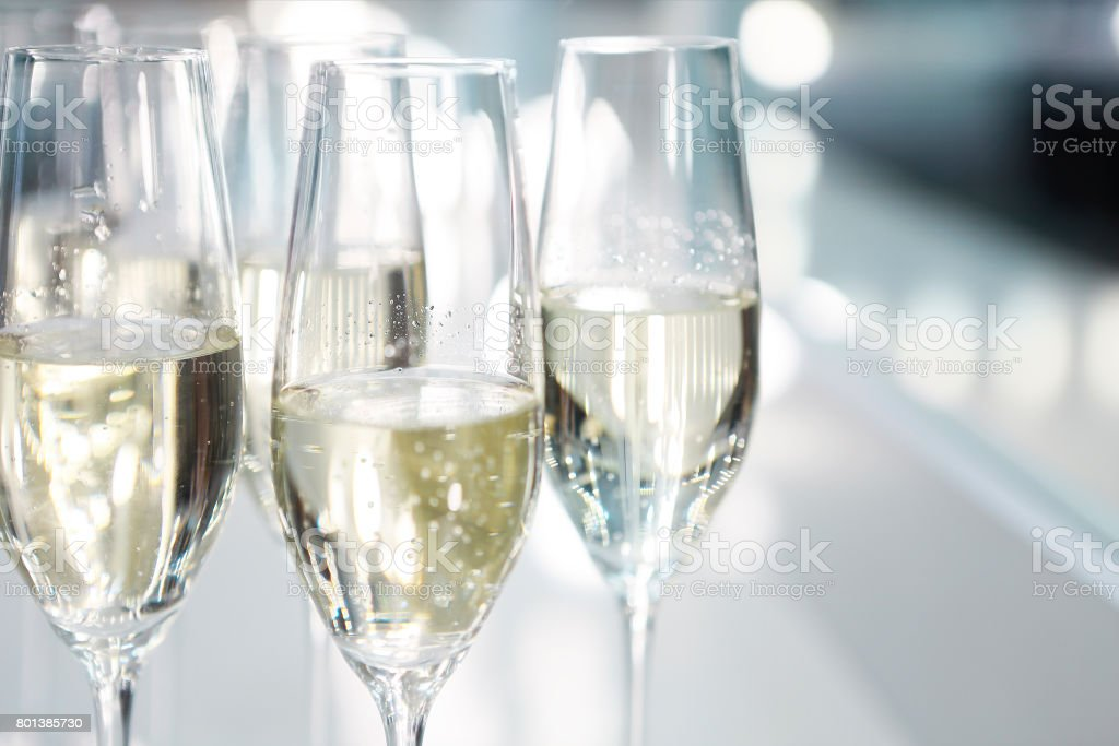 Champagne glasses on white background in bright lights stock photo