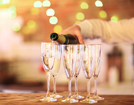Champagne glasses on wooden table in bright lights