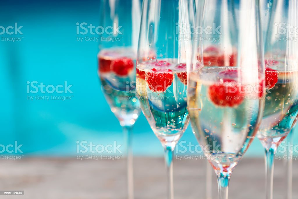 Champagne glasses with raspberry stock photo