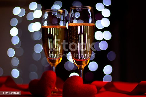 Champagne in glasses of two in romantic valentine concept with heart shaped fabric on red and light bokeh background