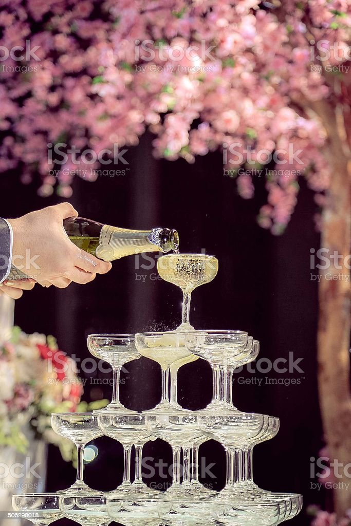 Champagne poured on the top of Champagne tower stock photo