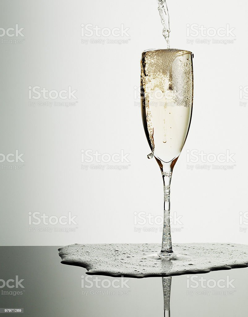 Champagne pouring into glass and overflowing royalty-free stock photo