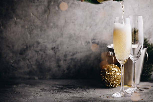 Champagne pouring into glasses and Christmas decorations