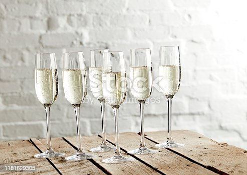 Shot of champagne served in glasses over wooden table