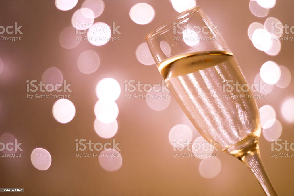 Champagne sparkling wine glass in disco party at night with defocused festive Christmas and New Year lights in nightclub stock photo