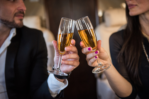 Close up shot of champagne glasses that business couple is holding inside the private jet aeroplane.