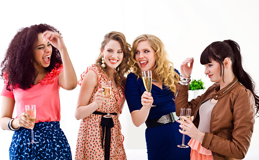Four pretty, well dressed young adult girlfriends holding glasses of champagne and laughing. Studio shot, white background.