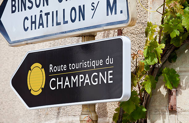 Champagne Tourist Route A road sign marks one of the official Tourist Route through the Champagne region around Reims and Epernay in northern France. A champagne grape vine twines itself up the wall of the building behind. marne stock pictures, royalty-free photos & images