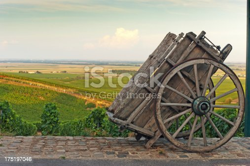 Late summer vineyards of a Premiere Cru area of France showing the lines of vines in the background and diagonal vines in the foreground. The village of Cramant is in the foreground with an old wooden cart used to transport grape harvests to the factory.