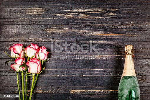 Champagne. Women's Day, 8 March. Champagne and roses on a wooden table. Valentine's Day. Birthday. Wedding. Anniversary. Rustic style