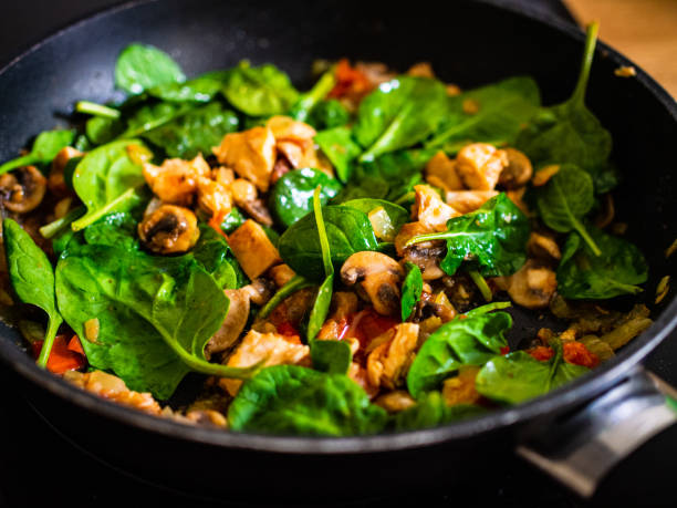 Champignon mushrooms fried with spinach, meat, tomato and onion in pan stock photo