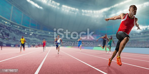 Wide angle, shallow depth of field image of a professional male track athlete sprinting over the finish line of a race with his arms outstretched in victory with composed expression. The athlete is competing in an indoor track sprint event in a generic arena, and finishes ahead of his competitors.