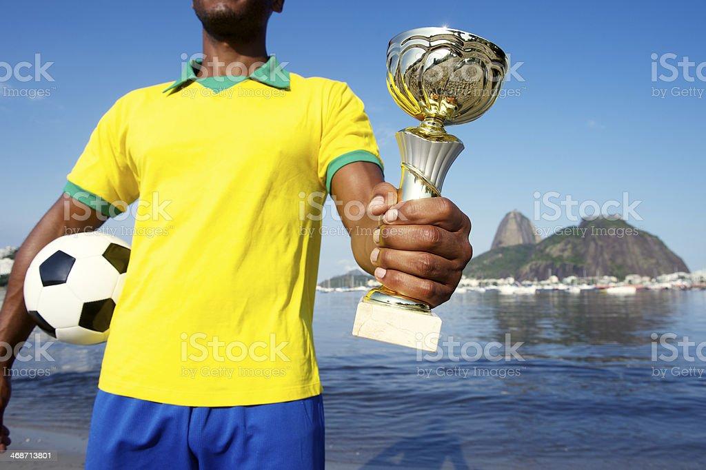 Campeão Jogador de futebol brasileiro segurando o troféu e futebol - foto de acervo