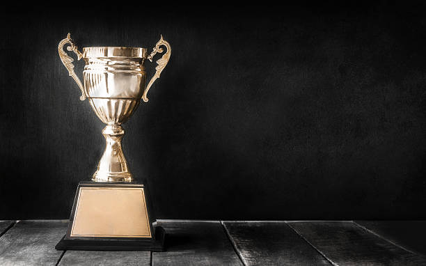 champion golden trophy on wood table with blackboard copy space stock photo
