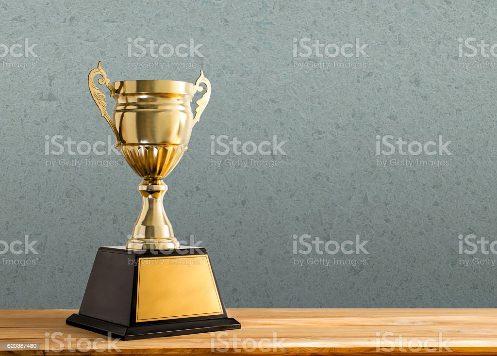 champion golden trophy on wood table with copy space, stock photo