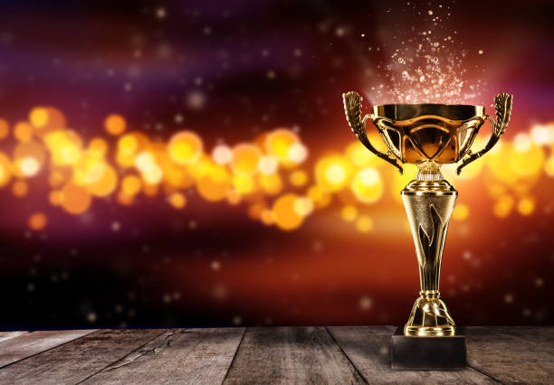 Champion golden trophy on wood table with spot lights on background stock photo