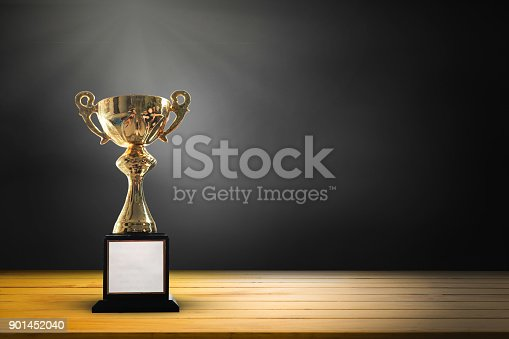 932724052 istock photo Champion golden trophy on wooden table background. copy space for text. 901452040