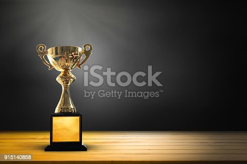 istock Champion golden trophy on wooden table background. copy space for text. 915140858