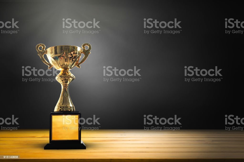 Champion golden trophy on wooden table background. copy space for text. stock photo