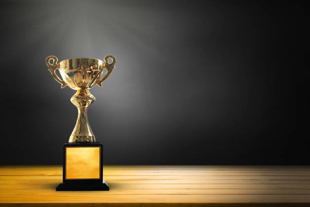 champion golden trophy on wooden table background. copy space for text. - trophy award stock photos and pictures