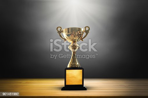 932724052 istock photo Champion golden trophy on wooden table background. copy space. 901451992