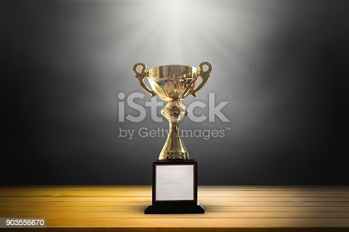 932724052 istock photo Champion golden trophy on wooden table background. copy space. 903556670