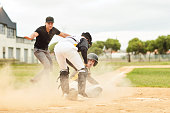 Full length shot of a young baseball player sliding on the pitch and safely reaching base during a game outdoors