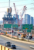 This vertical, very 'busy' shot, shows cranes working on the new Champlain Bridge, with traffic in the foreground and some Montreal city skyline behind.