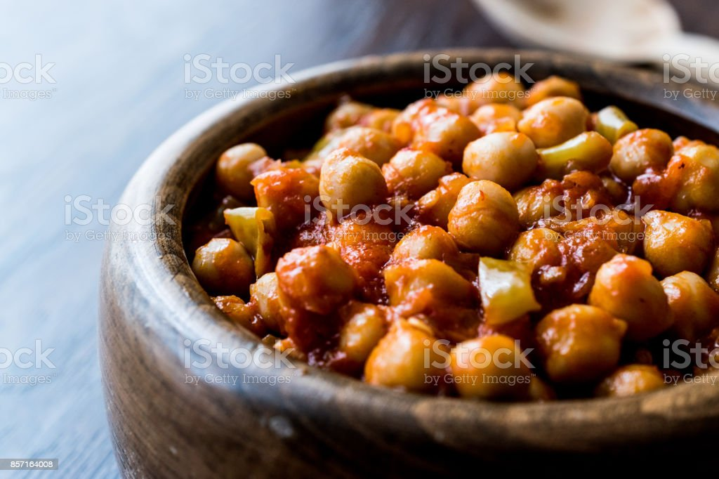 Chana Masala Chickpeas in wooden bowl. stock photo