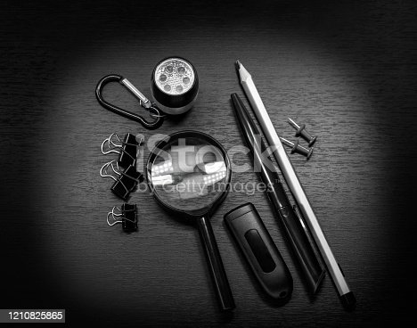 Chancery on a wooden table, magnifier, pen, pencil, binders clip, paper clip, flashlight, flash drive and buttons. Set of detective. Black and white photo. Selective focus.