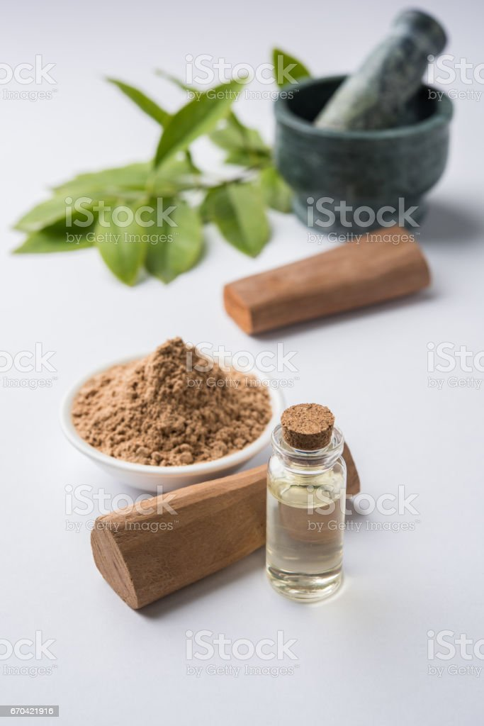 Chandan or sandalwood powder with traditional mortar, sandalwood sticks, perfume or oil and green leaves. selective focus stock photo