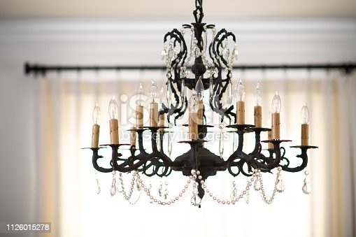 Electrical Candlestick chandelier with crystals hangs from the ceiling of a dining room.
