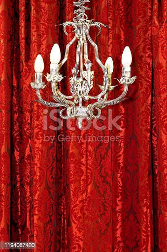 Old rusty metal chandelier over red drapery
