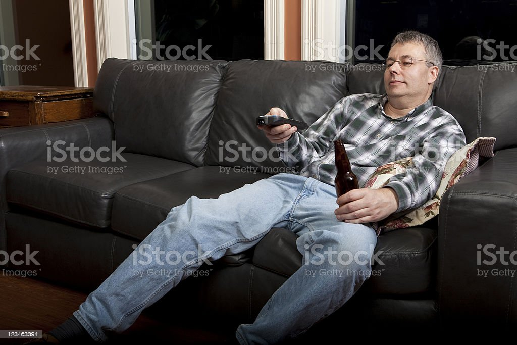 Chanel surfing couch potatoe drinking beer royalty-free stock photo