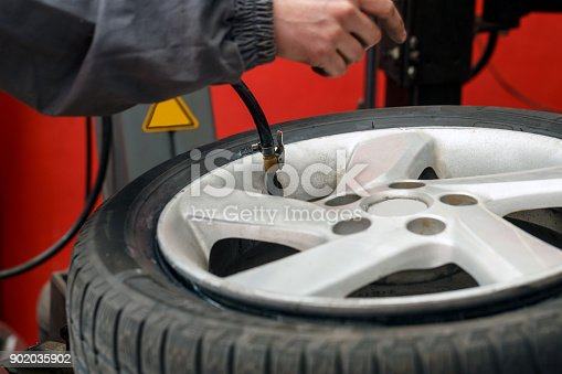 498888104 istock photo Change a tire, Car mechanic is changing a tire 902035902