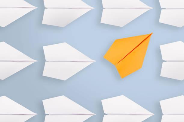 change concepts with orange paper airplane leading among white - zmiana zdjęcia i obrazy z banku zdjęć