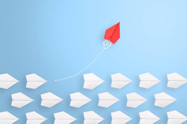 ändern sie konzepte mit rotem papierflugzeug, das unter weiß führt - individualität stock-fotos und bilder