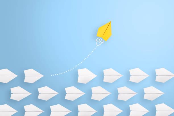 ändern sie konzepte mit gelbem papierflugzeug, das unter weiß führt - anleitung konzepte stock-fotos und bilder