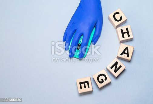 613303142 istock photo change inscription on wooden cubes and a hand in a blue medical glove with a computer mouse on a gray-blue background 1221393130