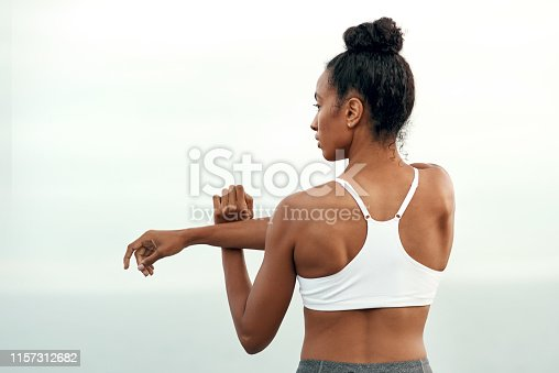 Rearview shot of a sporty young woman stretching her arms while exercising outdoors