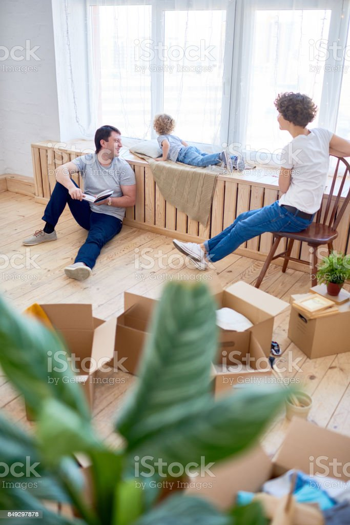 father reading book, mother and son looking out window