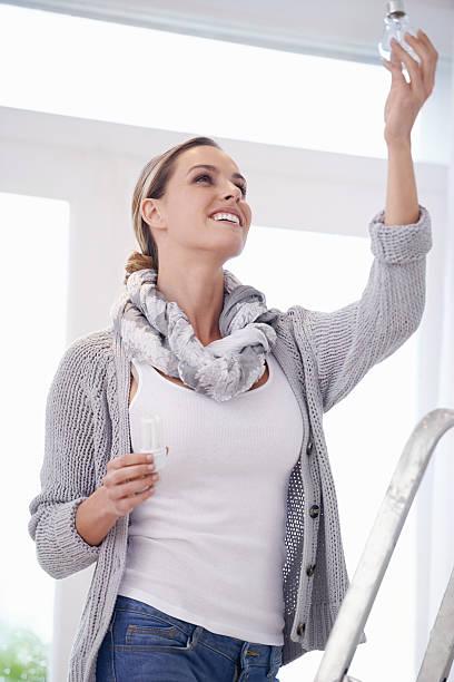 ändern einer glühbirne ist kein problem für damen - glühbirne auswechseln stock-fotos und bilder