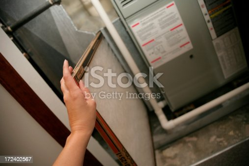 Female hand sliding a new air filter into a furnace.