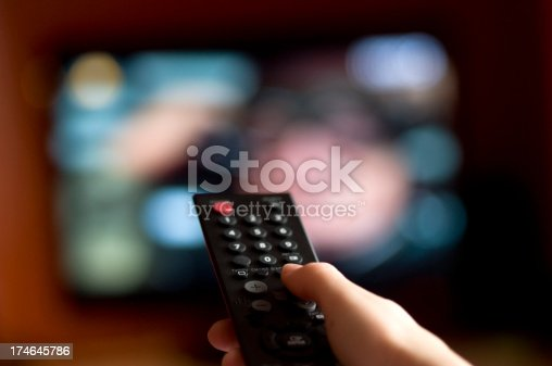 Focused on the hand holding a remote control with a television in the background.