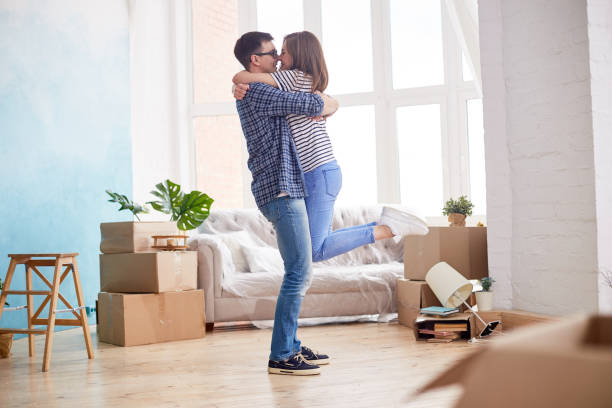 Changing Life for Better Profile view of loving young couple expressing their feeling while standing at living room of new apartment, interior design items and moving boxes on background two parents stock pictures, royalty-free photos & images