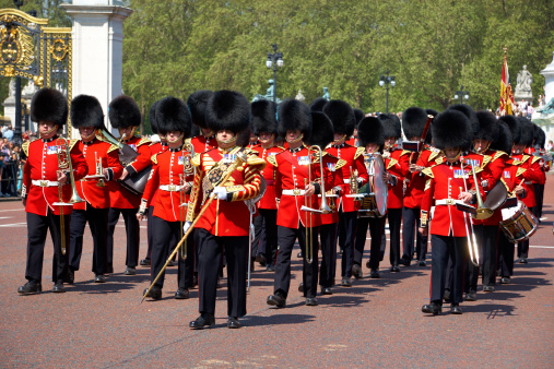 London, England - July 2018: Crowd of People gathered outside the railings of Buckingham Palace for the changing of the guard ceremony.