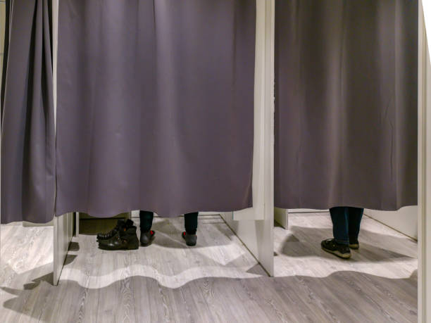 Changing room with closed curtains and feet of two customers