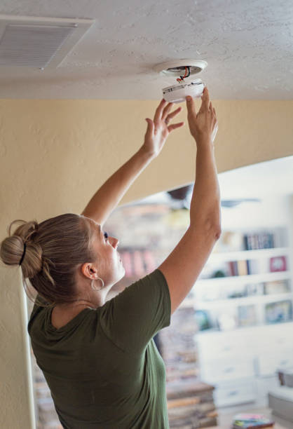 Changing the battery on a smoke alarm in an interior of a home stock photo