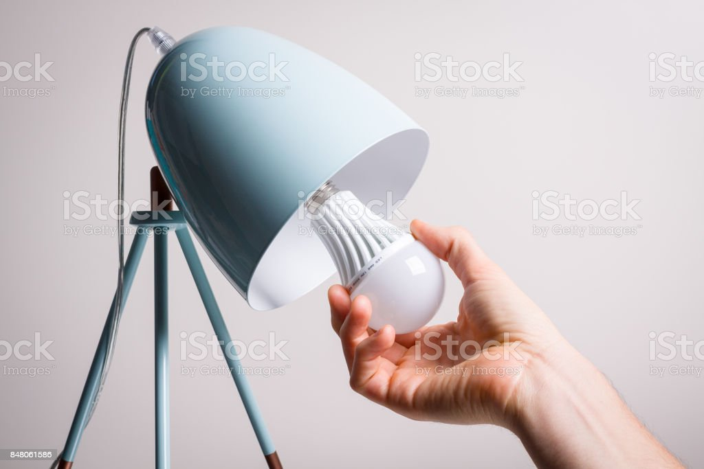 Changing the bulb for led bulb in table lamp in turquoise colours. stock photo