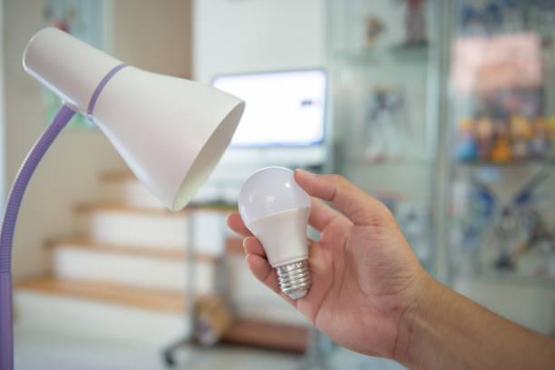 die glühbirne auf led wechseln, um in der lampe zur energieeinsparung zu installieren - glühbirne auswechseln stock-fotos und bilder